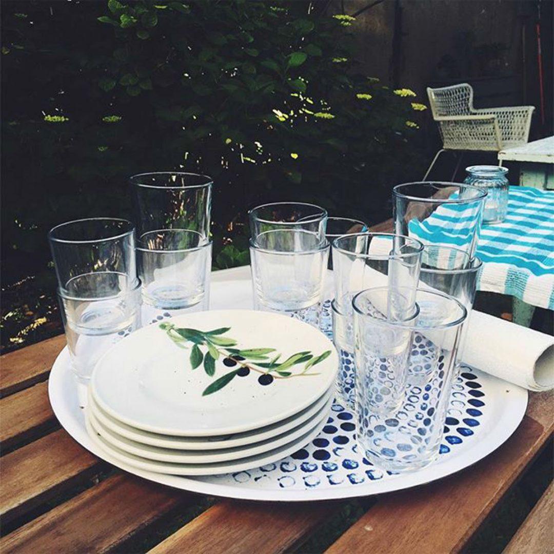 Teller und Gläser auf einem Tablett auf einem Gartentisch