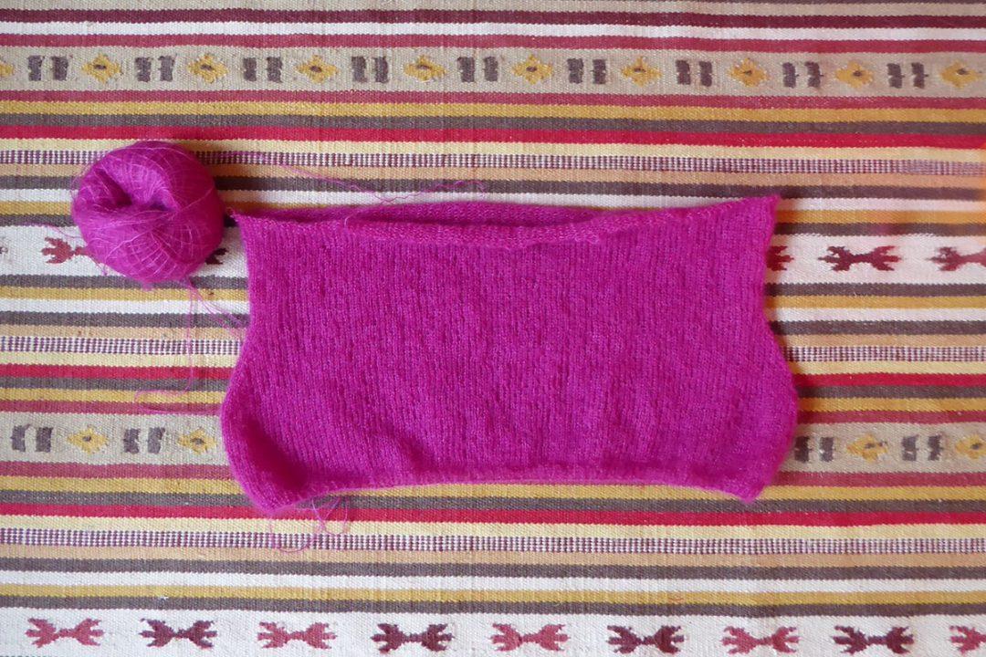 Ein Strickzeug aus pinkfarbener Mohairwolle liegt auf einem Kelimteppich