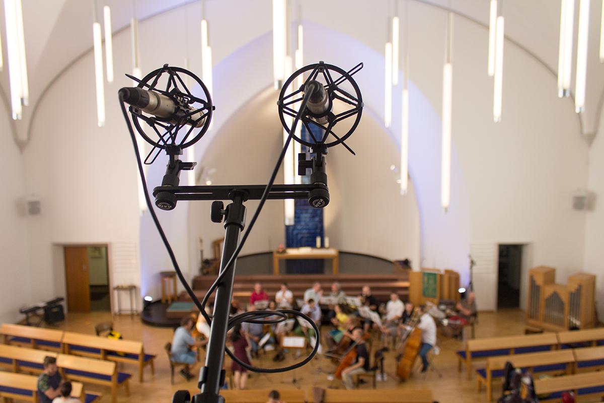 In einer Kirche: Im Vordergrund Mikrofone dahinter schemenhaft ein Kammerorchester