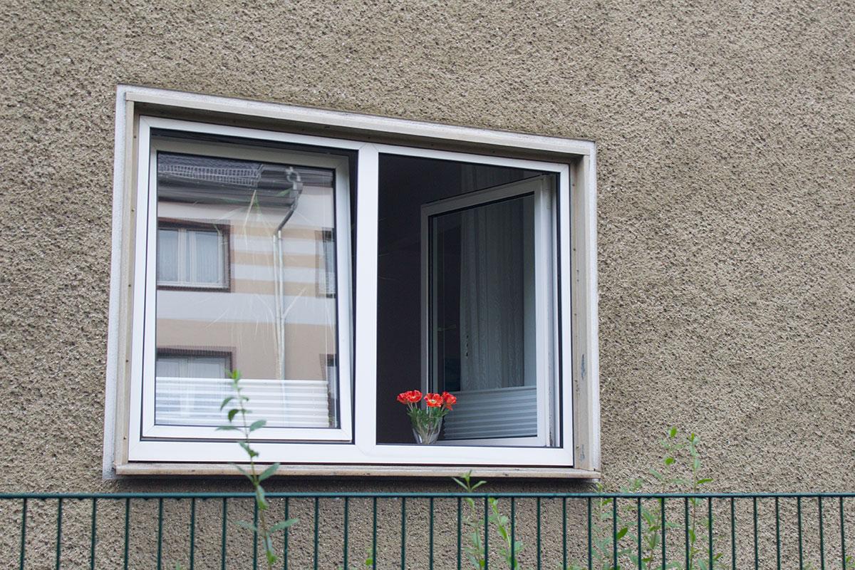 Ein offenstehendes Fenster einer Häuserfront mit einem kleinen roten Blumenstrauß auf der Fensterbank aufgenommen im Kreuzviertel Dortmund