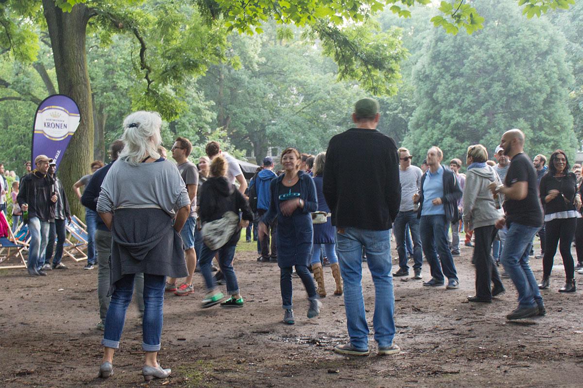 Tanzende Menschen auf einer nassen Wiese aufgenommen im WEstpark Dortmund