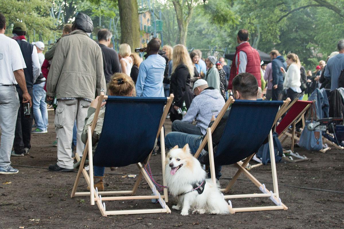 Eine Ansammlung von Menschen davor zwei Personen in einem Liegestuhl und ein Hund aufgenommen im Westpark Dortmund