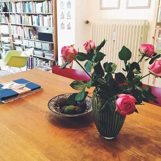 Blumen, eine Schale mit Avocados und diverse Unterlagen stehen bzw.liegen auf einem Esstisch
