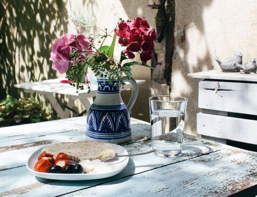 Blumen in einer bunt bemalten Vase, ein Snack auf einem Teller und ein Glas Wasser stehen auf einem Gartentisch