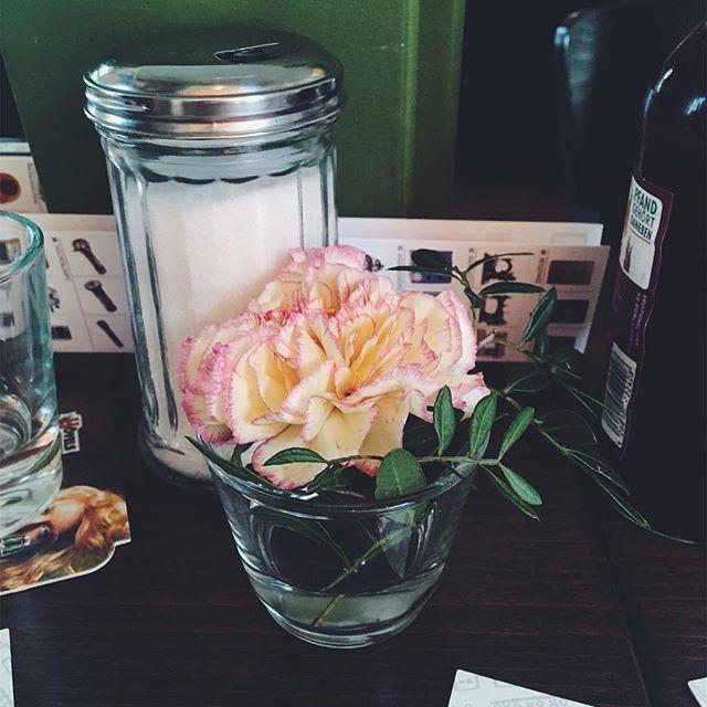 Ein Wasserglas mit einer Nelke darin steht vor einer Zuckerdose