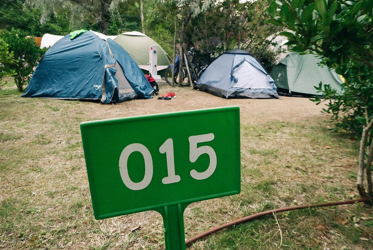 Drei Zelte auf einem Campingplatz davor ein Schild mit der Nummer 015