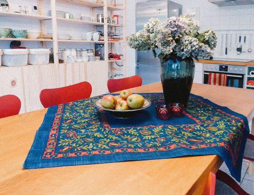 Ein bunt bedruckte Decke liegt auf einem Tisch darauf eine Schale mit Äpfeln und eine Vase mit getrockneten Hortensien
