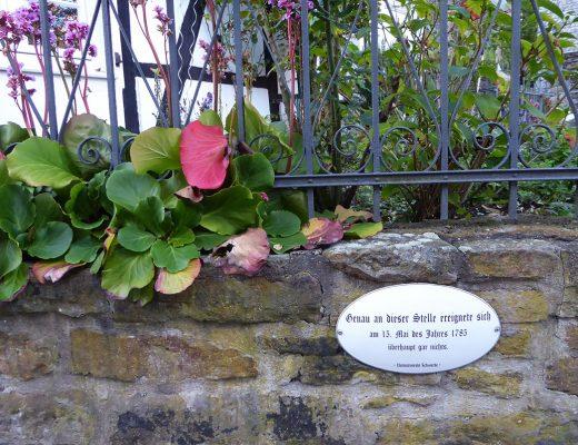 """Eine Mauer aus Natursteinen, daran ein ovales Schild mit der Aufschrift """"Genau an dieser Stelle ereignete sich am 13. Mai des Jahres 1783 überhaupt gar nichts."""