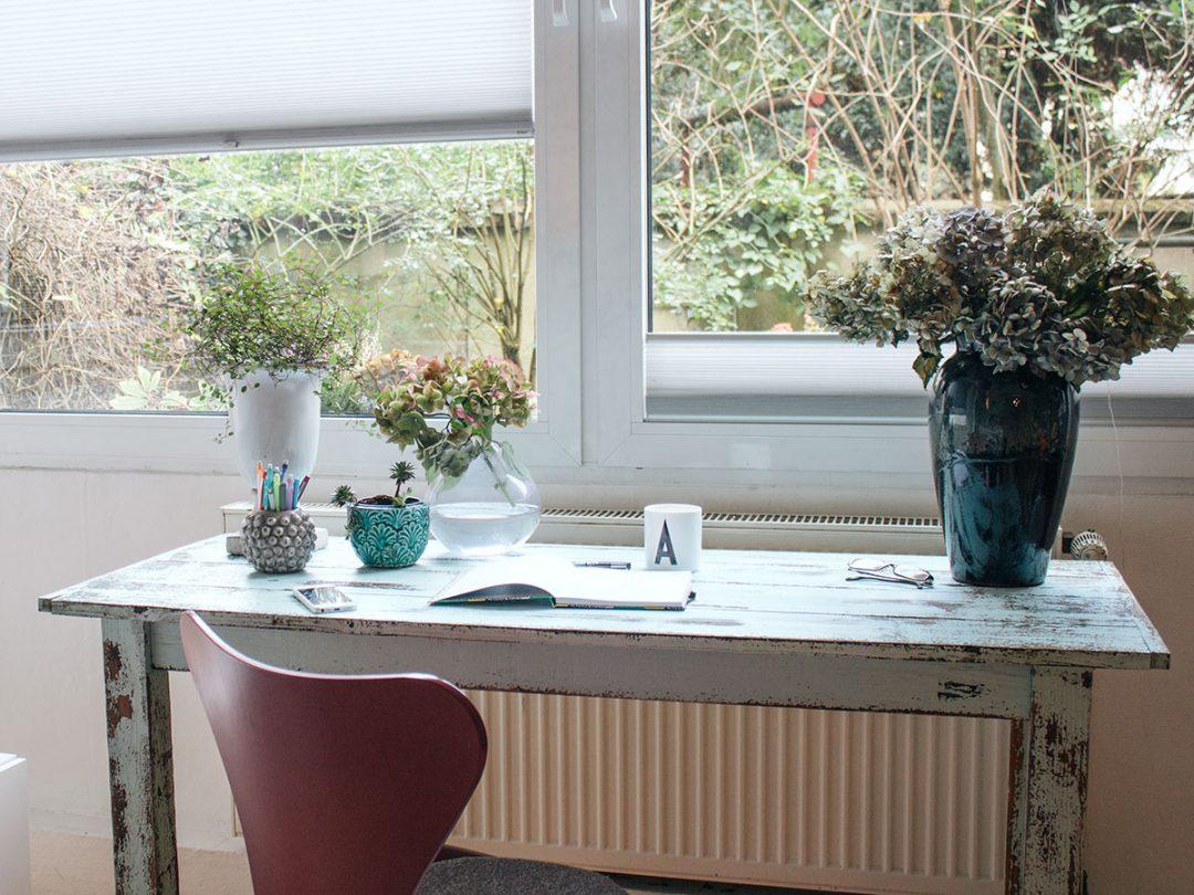 Ein Schreibtisch im Shabby-Chic-Look steht vor einem Fenster darauf Vasen in unterschiedlichen Formen