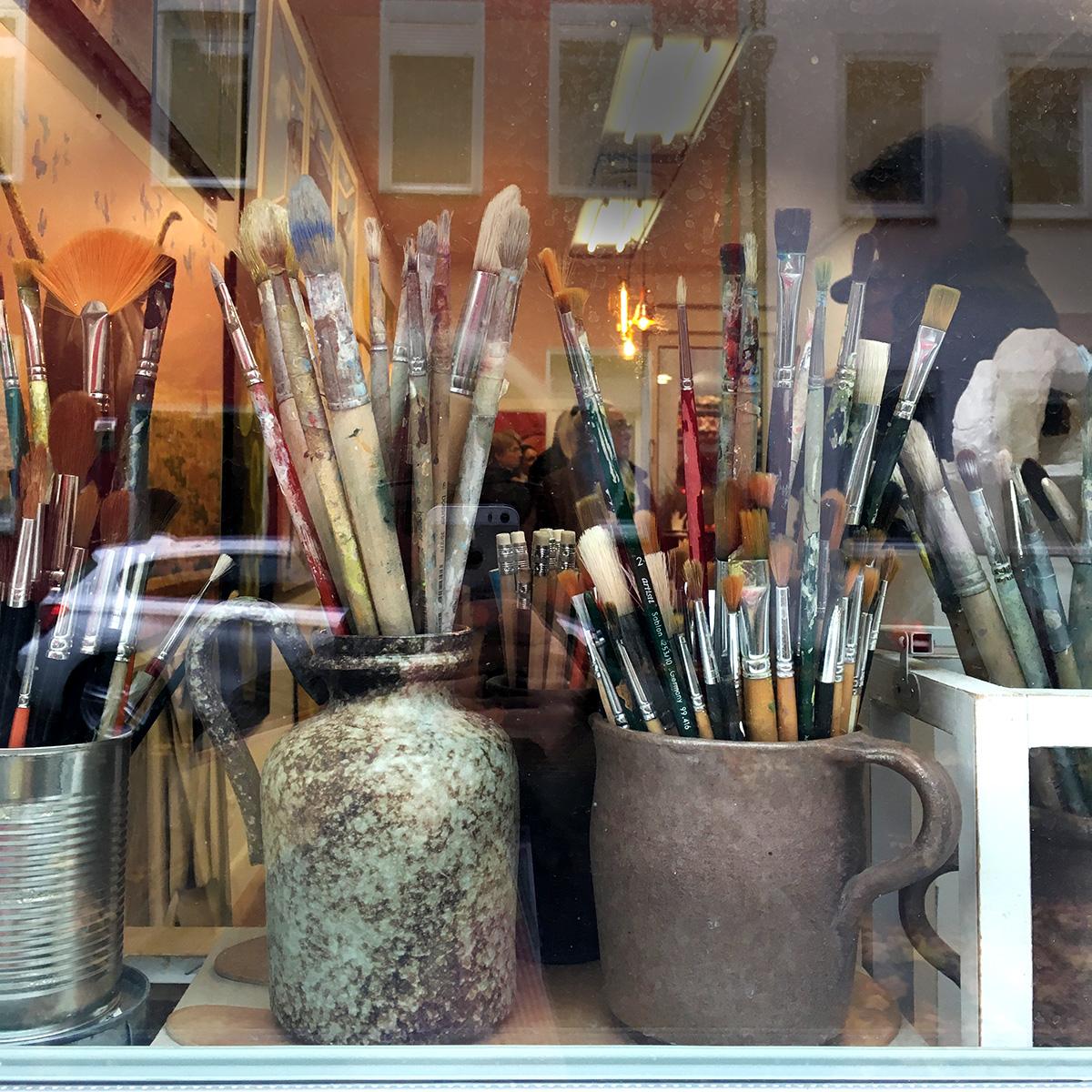 Blick durch eine Fensterscheibe in ein Ladenlokal im Vordergrund Behälter mit vielen verschiedenen Pinseln