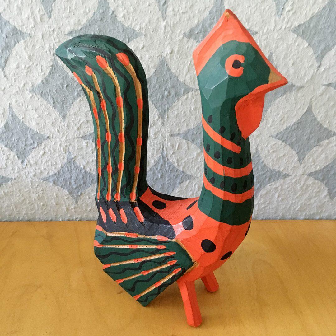 Ein geschnitzter Hahn grün und rot bemalt
