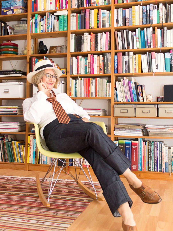 Frau in Jeanshose, weißem Hemd und Krawatte sitzt in einem Sessel vor einem Bücherregal