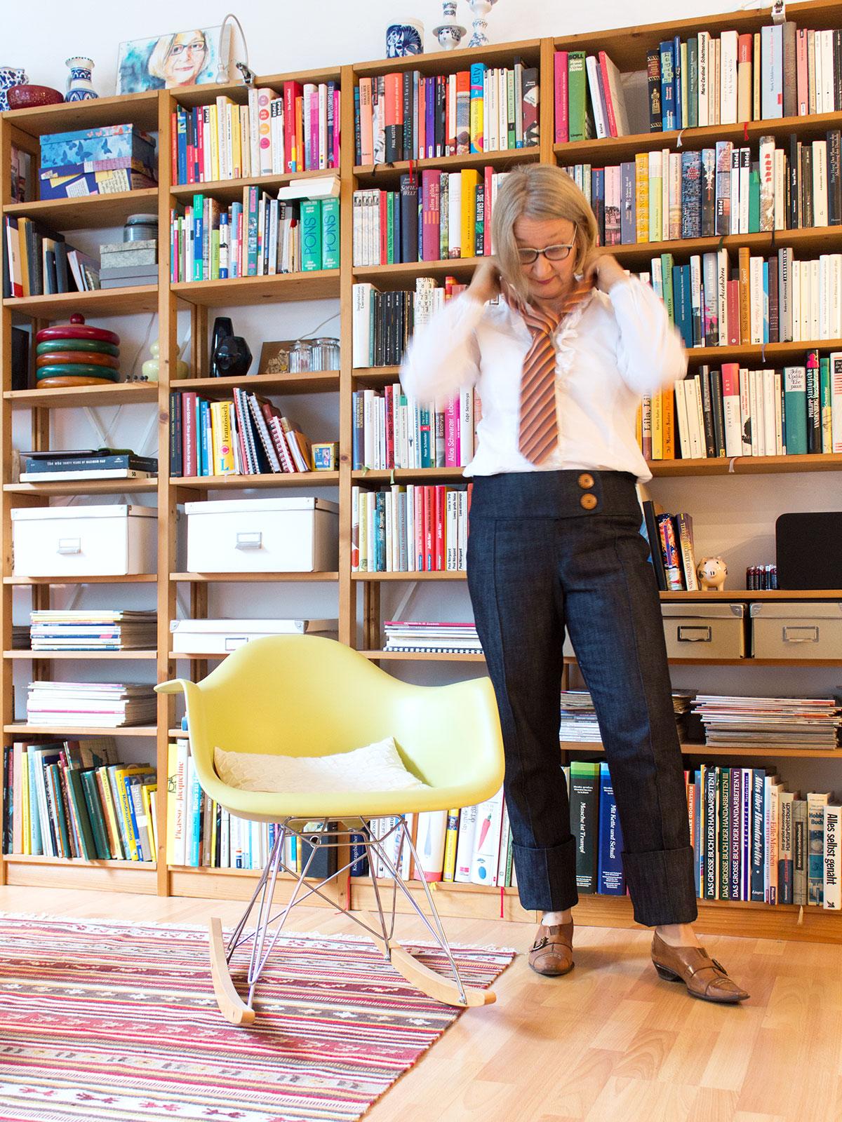 Frau in Jeanshose, weißem Hemd und Krawatte steht vor einem Bücherregal