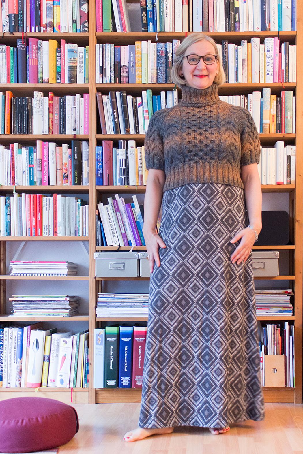 Eine Frau in einem handgestrickten Rollkragenpullover mit kurzen Ärmeln und einem langen Kleid steht vor einem Bücherregal