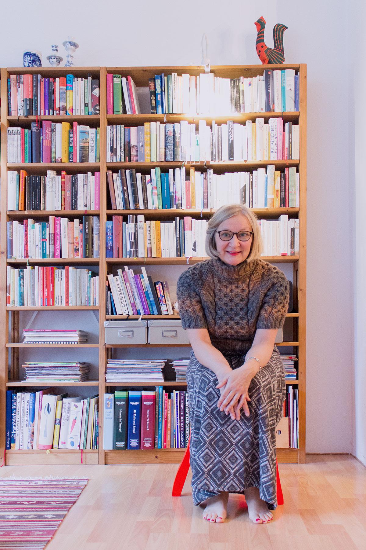 Eine Frau in einem handgestrickten Rollkragenpullover mit kurzen Ärmeln und einem langen Kleid sitzt auf einem Hocker vor einem Bücherregal
