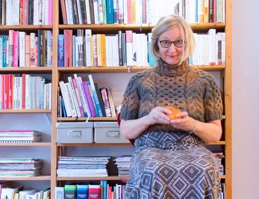 Eine Frau in einem handgestrickten Rollkragenpullover mit kurzen Ärmeln und einem langen Kleid sitzt auf einem Stuhl vor einem Bücherregal