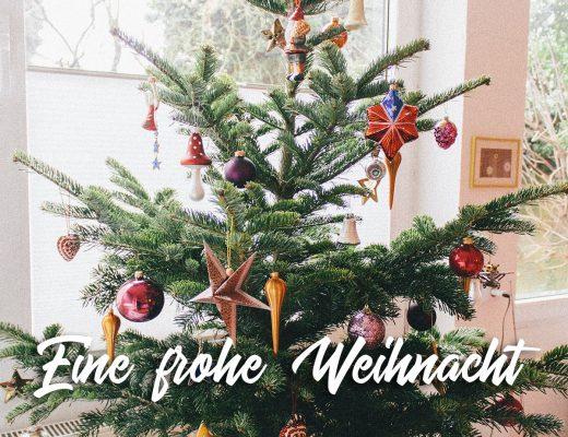 """Ein bunt geschmückter Weihnachtsbaum steht auf einem Tisch im Shabby-Chic-Look davor der Schriftzug """"Eine frohe Weihnacht"""""""