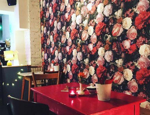 Foto ein roter Tisch steht vor einer mit Blumenmuster tapezierten Wand