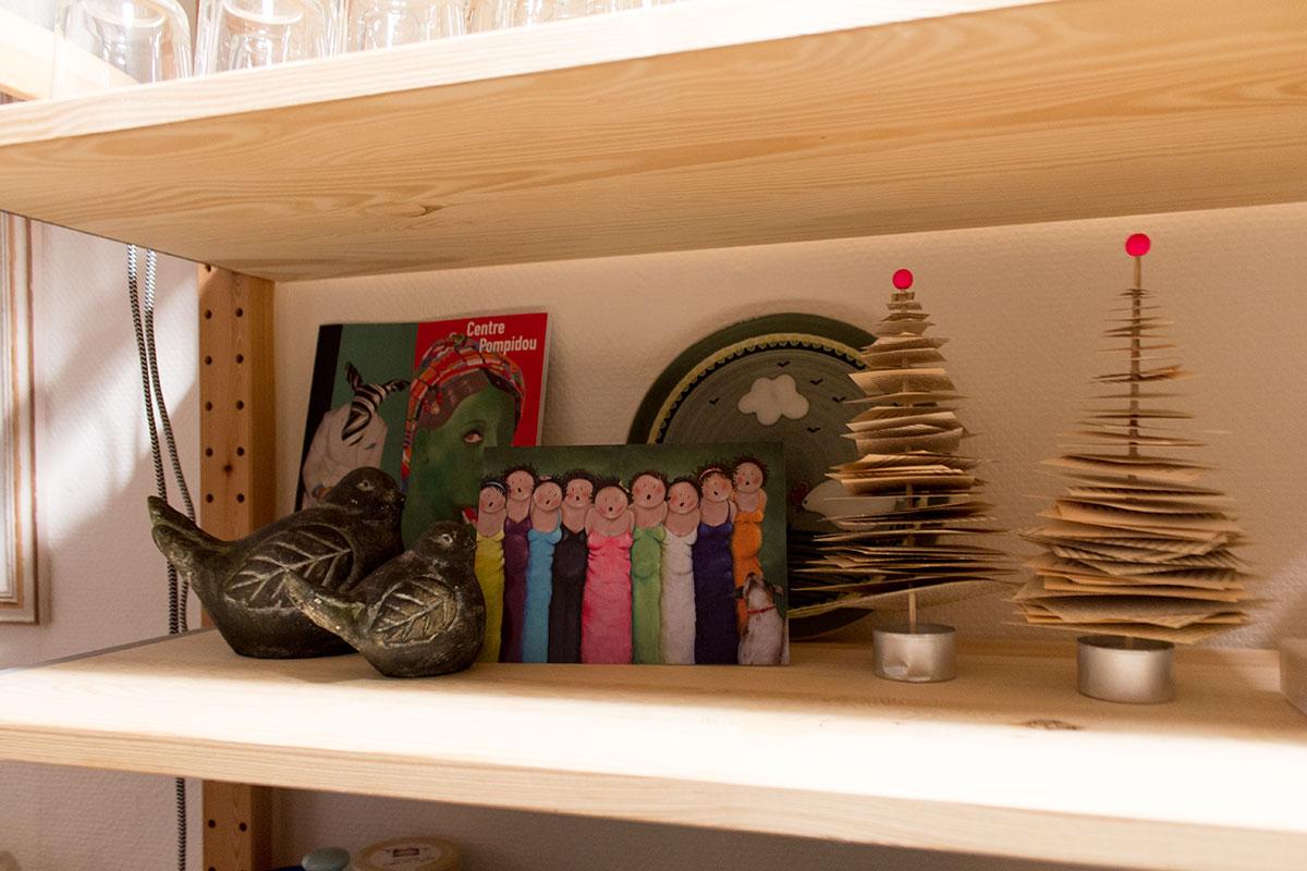 Blick in ein Regal, Vögel aus Stein, eine Postkarte mit einem gezeichneten Frauenchor, selbstgebastelte Weihnachtsbäume aus alten Büchern
