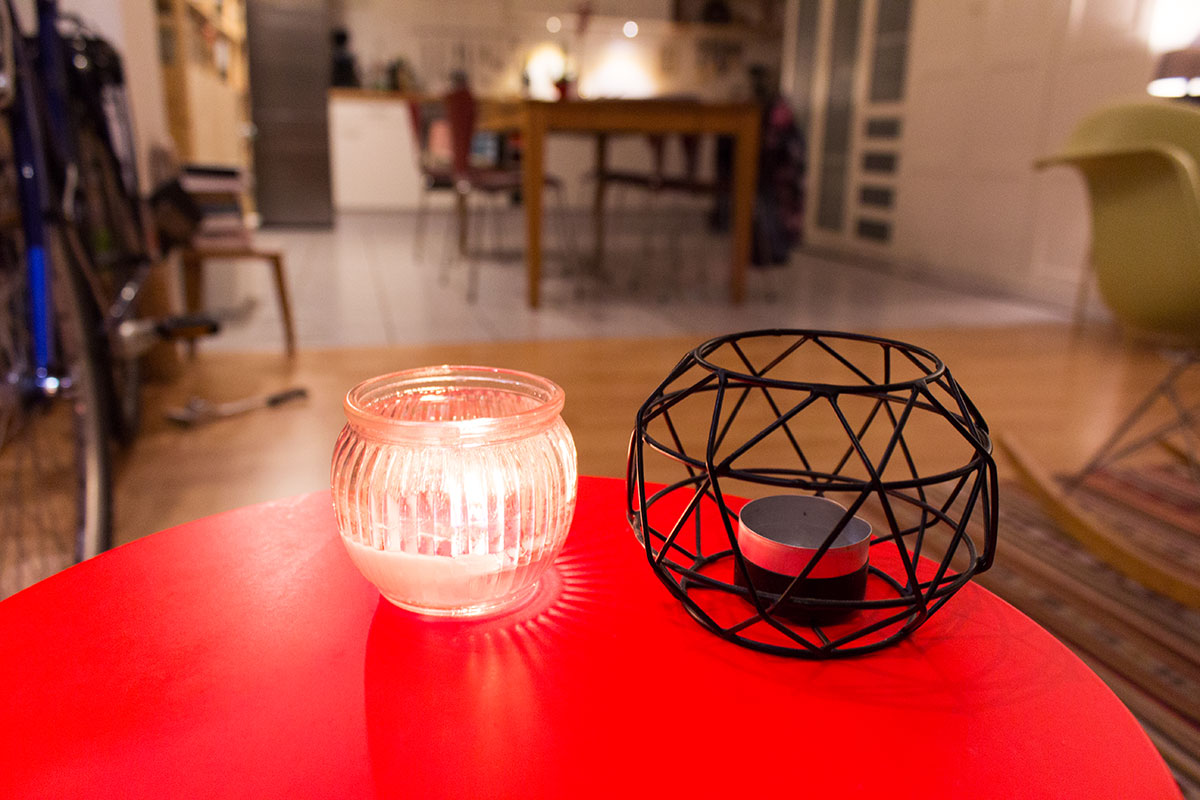 Zwei Teelichter stehen auf einem orangefarbenen Tisch