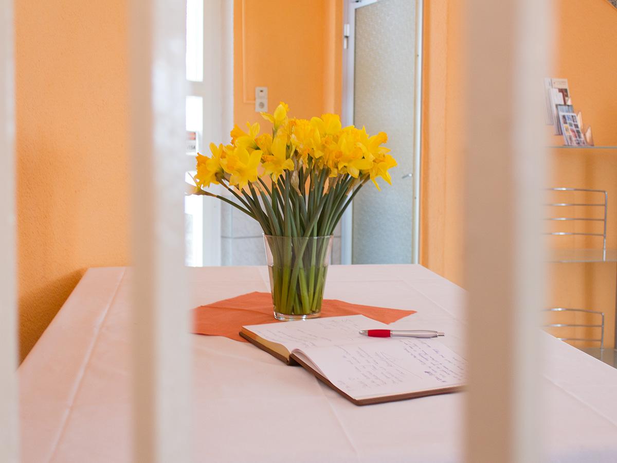 Ein Strauß Narzissen steht auf einem Tisch daneben liegt ein Gästebuch