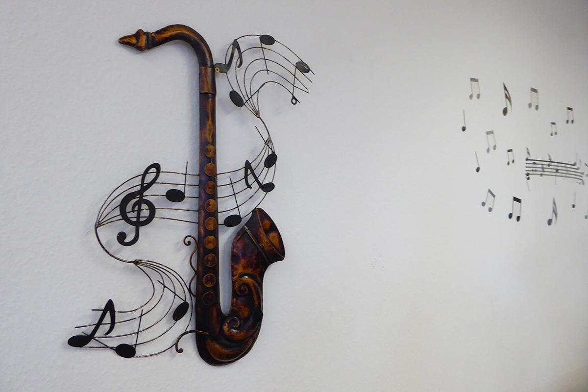 Ein stilisierte Saxophon hängt an einer Wand