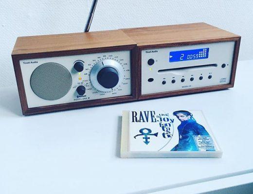 Ein Tivoli Audio Model One und Model TV stehen auf einem weißen Sideboard, davor liegt eine CD von Prince