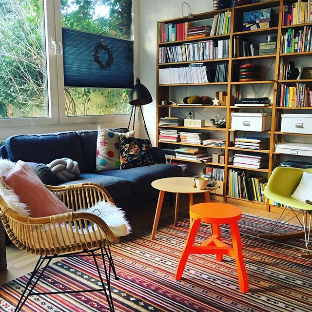 Ein Wohnzimmerinterieur mit Rattanstuhl, Eames Schaukelstuhl und IKEA Sofa
