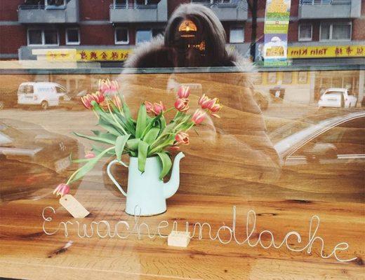 """Blick in ein Schaufenster im Vordergrund der Schriftzug """"Erwache und lache"""""""