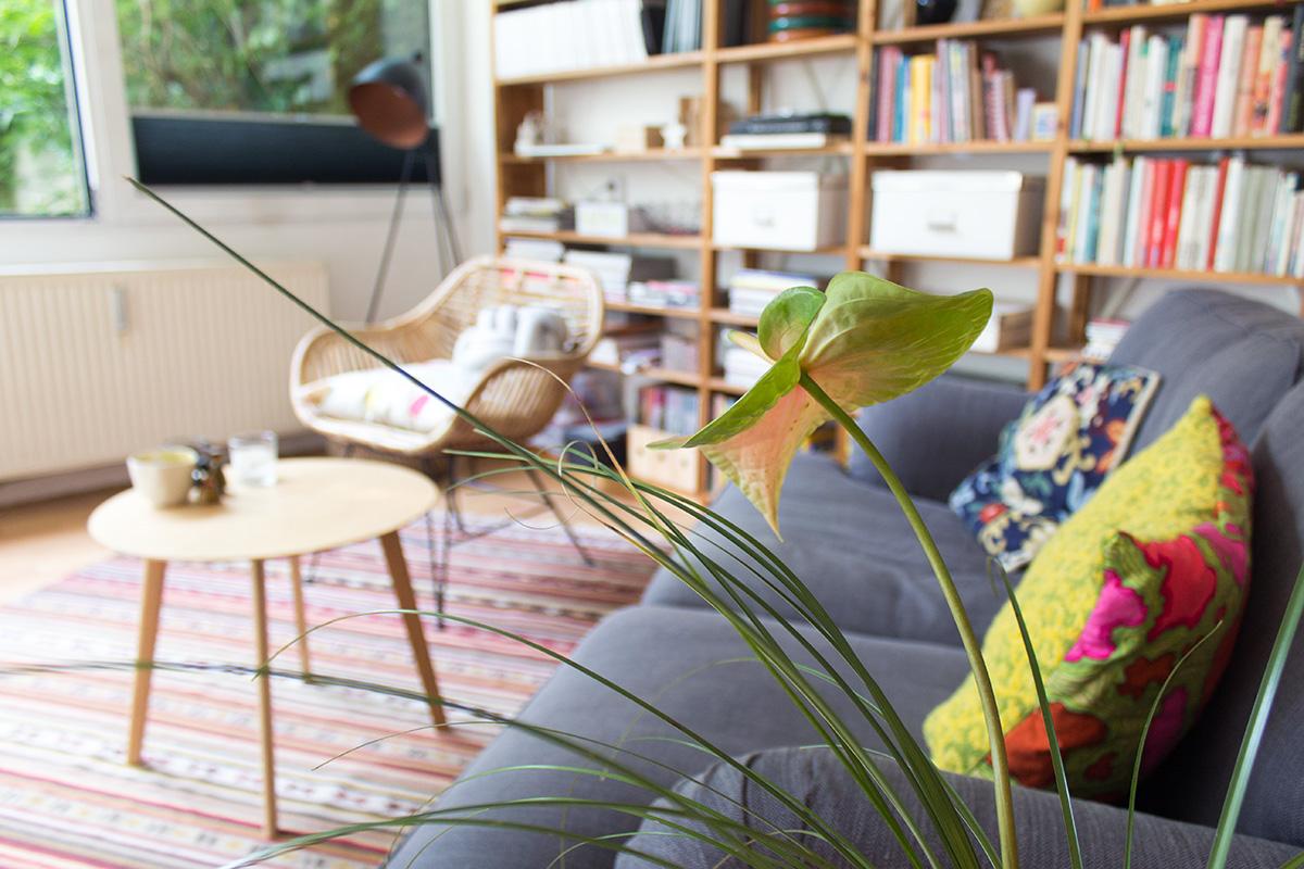 Wohnzimmersituation: Sofa, Coffetable, Rattansuhl, bunte Kissen, Bücherregal, IKEA Teppich