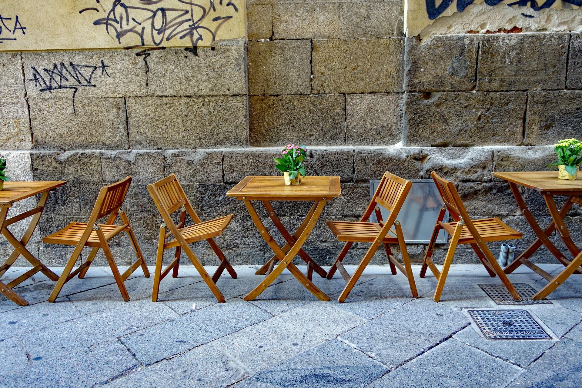Klappstühle und Holztische eines Straßencafes