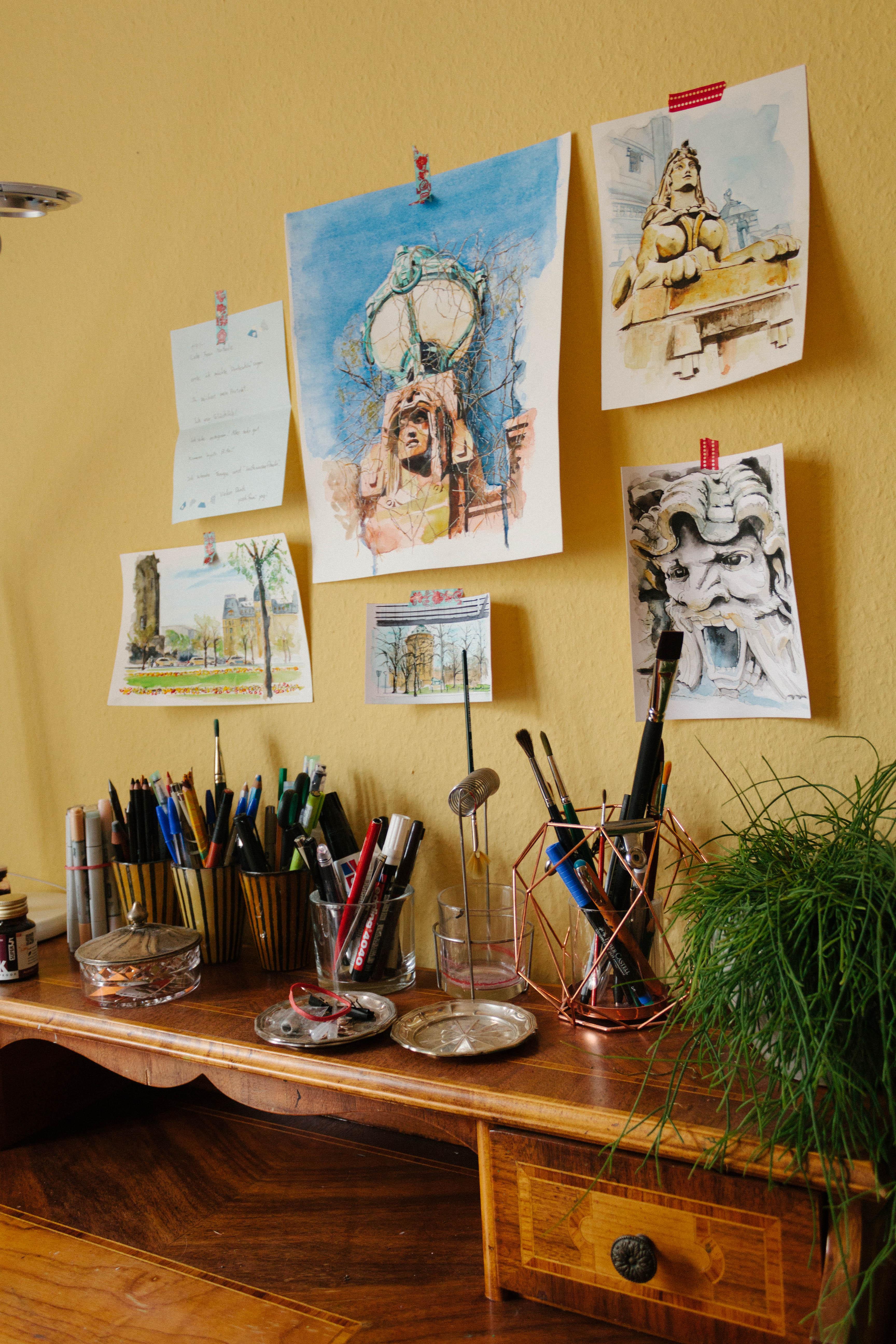 Aquarellbilder hängen an einer gelben Wand darunter ein Sekretär vollgestellt mit Behältern mit Pinseln