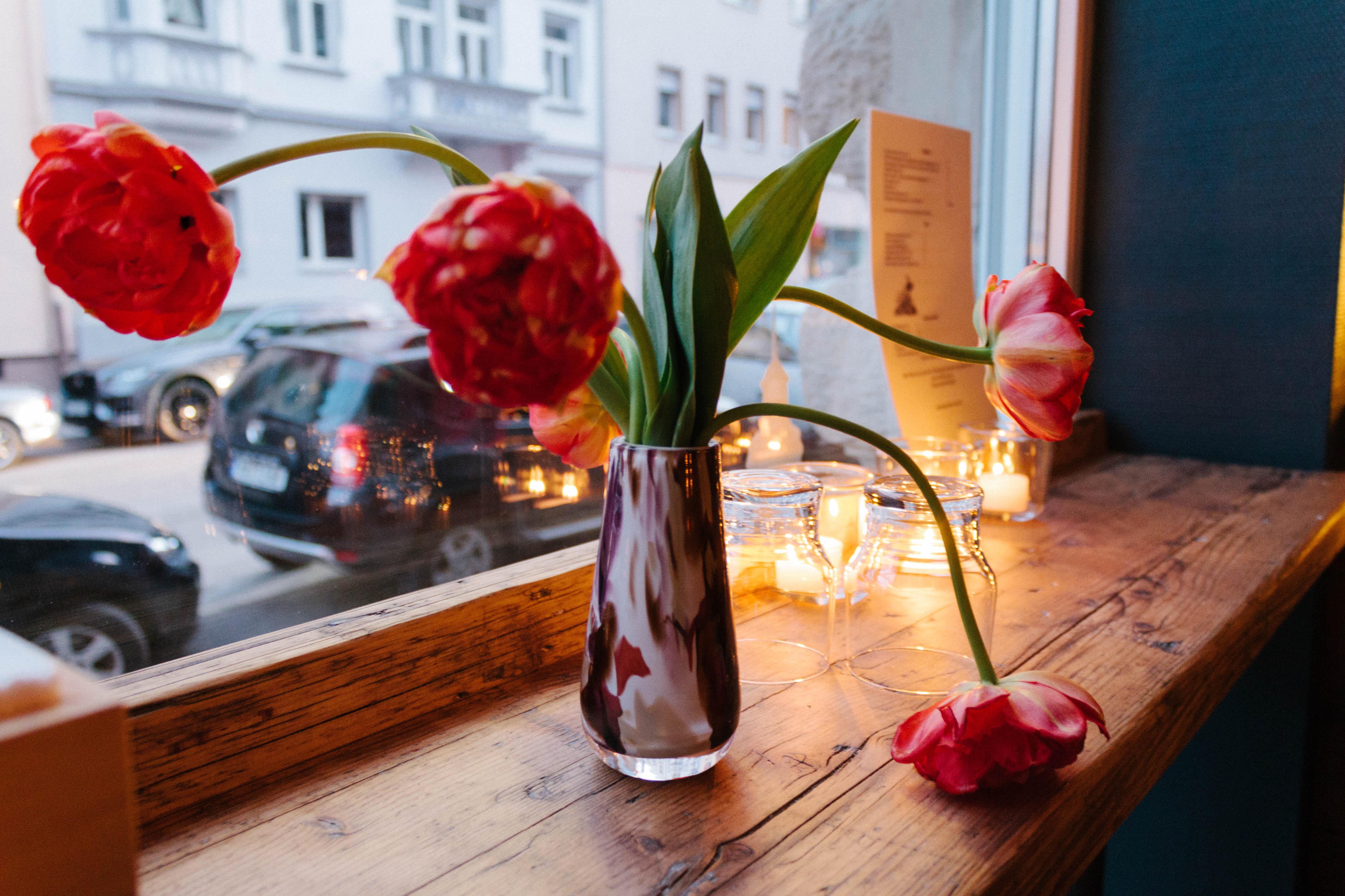 Tulpen in einer Muranoglasvase stehen auf einer Fensterbank aus grobem Holz