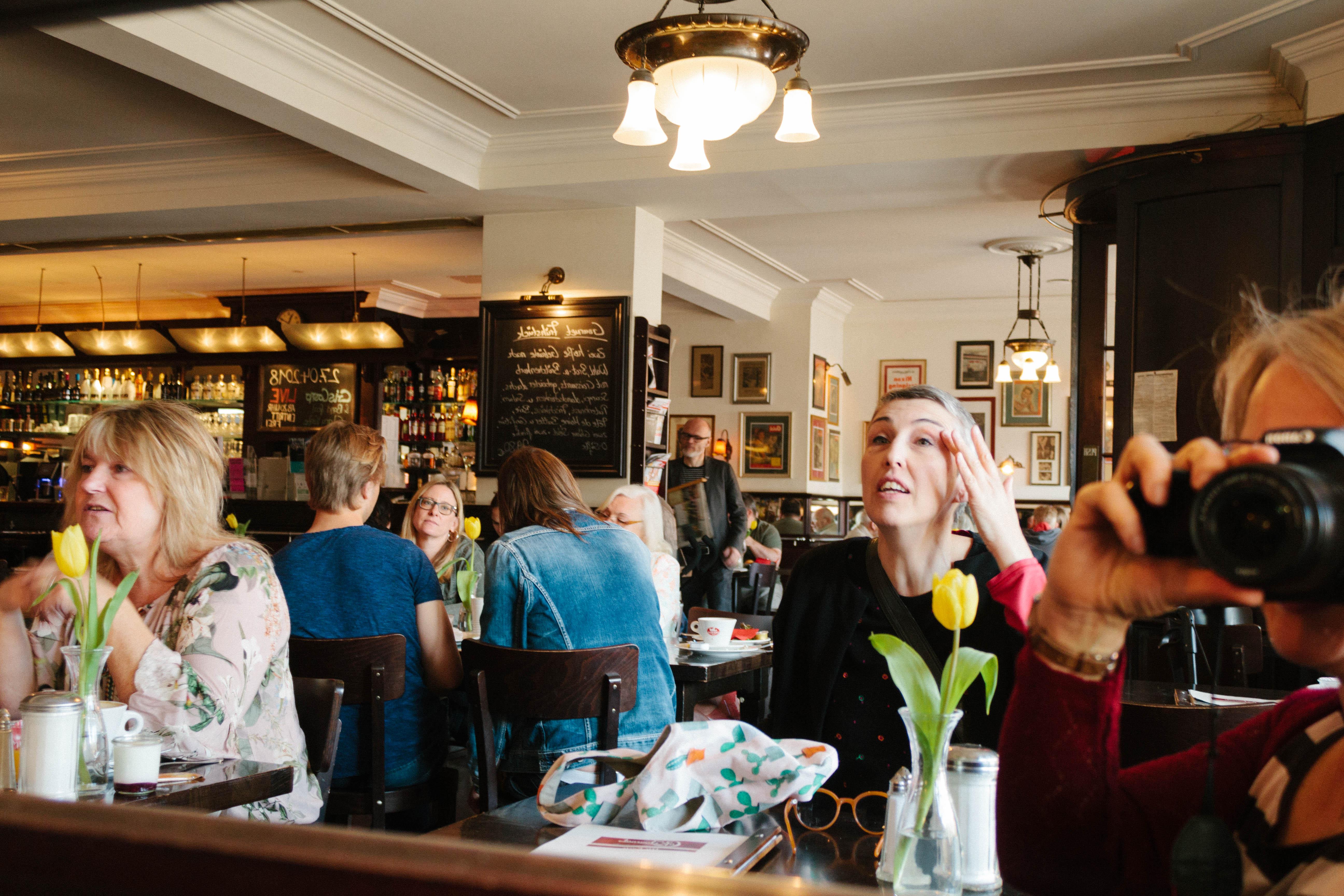 Eine Szene in einem oppulente Cafe: Eine Frau betrachtet sich im Spiegel
