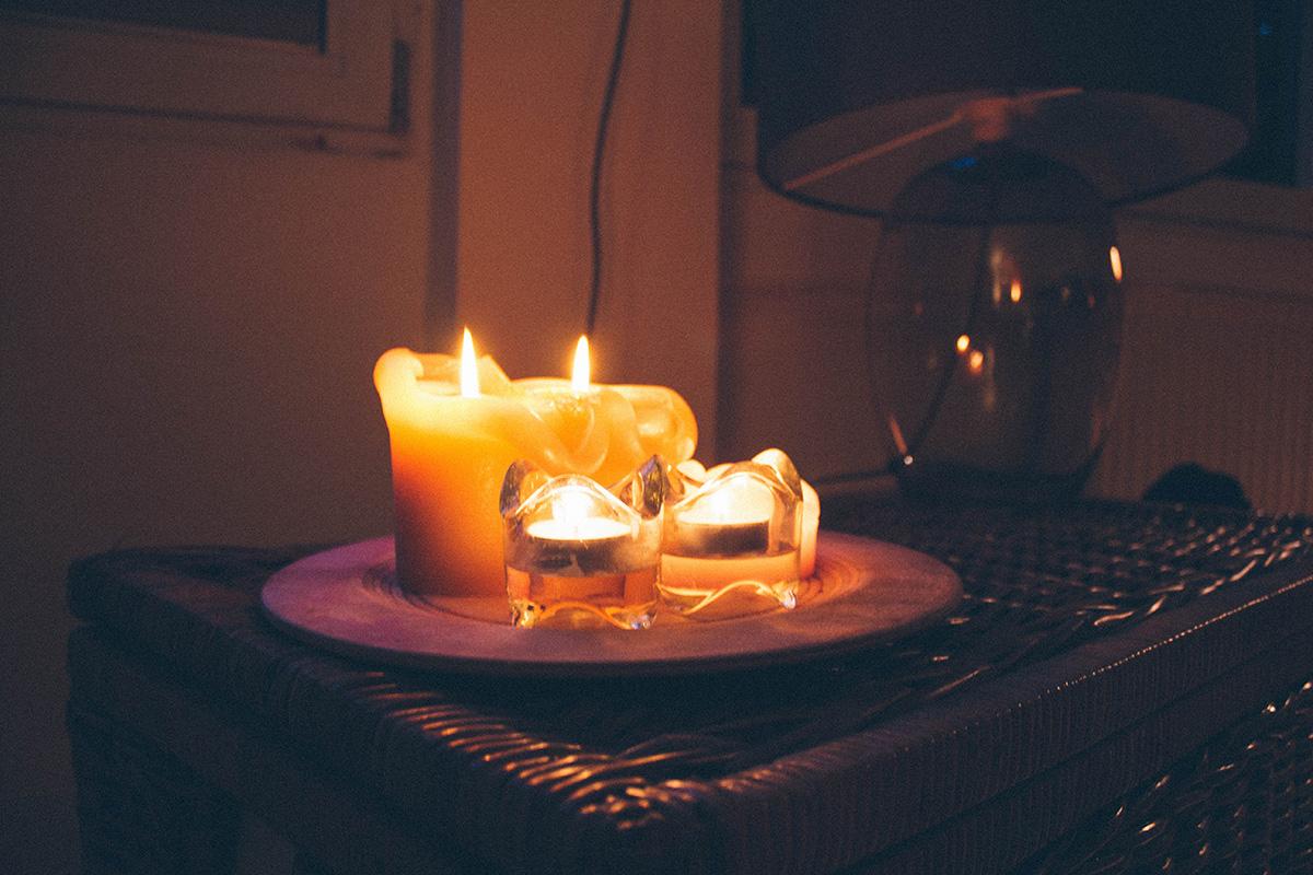 Mehrere brennende Kerzen stehen auf einem hölzernen Teller auf einer Weidentruhe