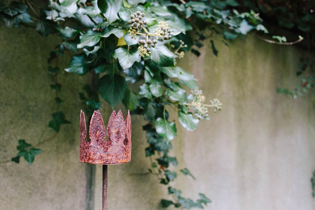 Herbstgarten - verrostete Gartenskulptur vor Efeu