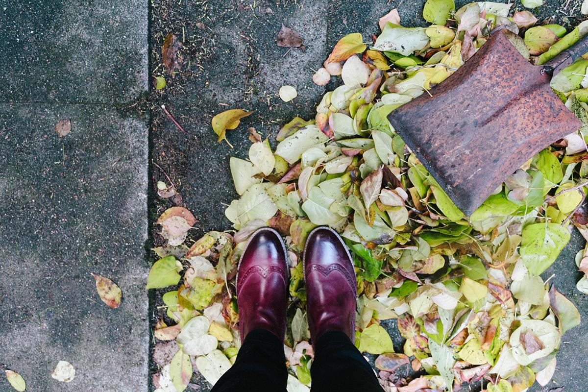 Herbstgarten - Stiefeletten stehen in einem Haufen Laub dazu eine verrostete Schaufel