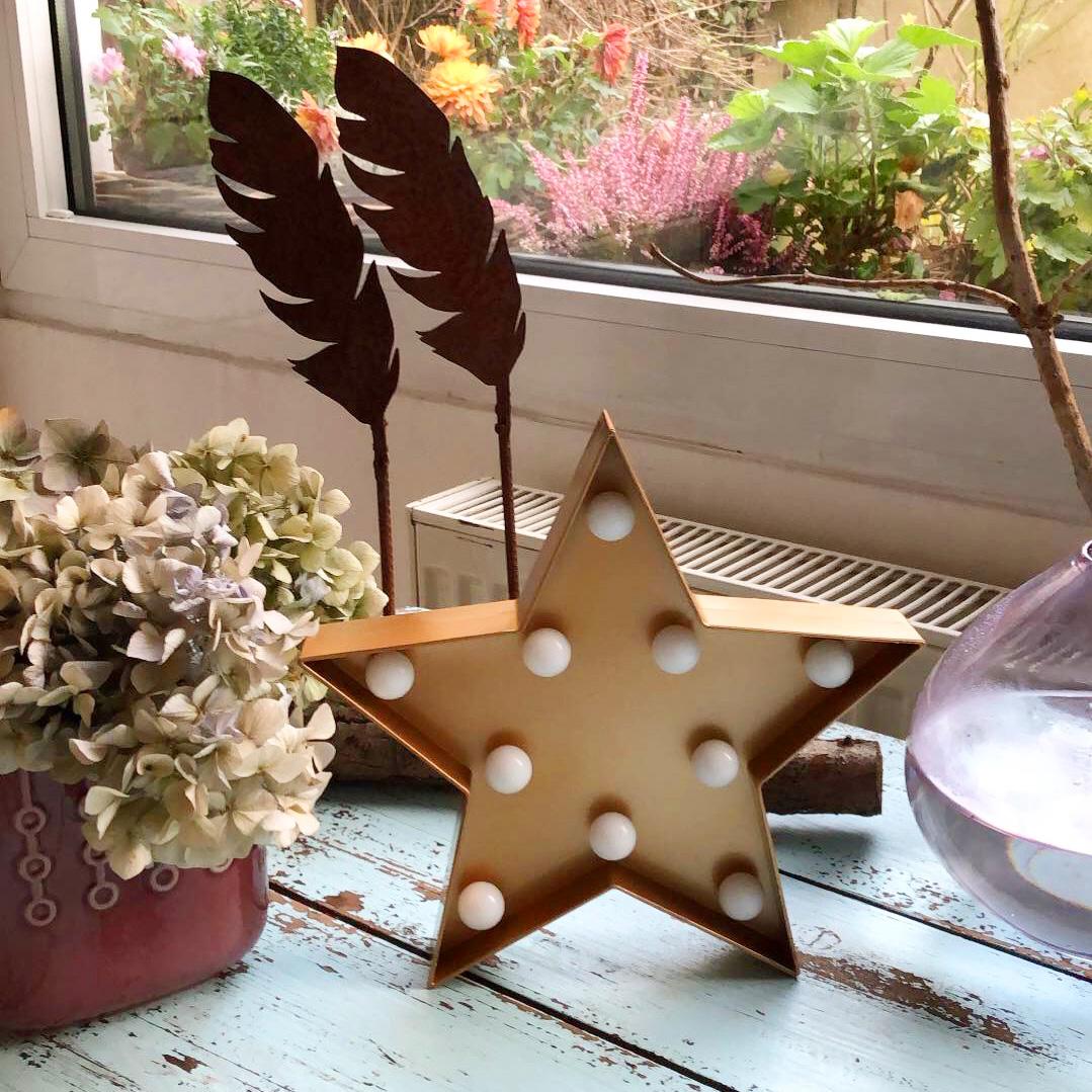 Weihnachtliche Innendekoration mit einem Stern mit Lämpchen