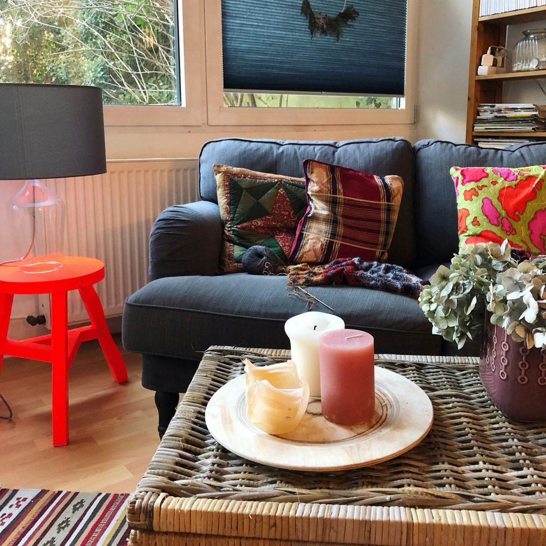 Ein Wohnzimmer mit einem Tom Dixon Hocker, einer Tischleuchte mit Glasfuß einem Sofa mit bunten Kissen einem Korb und einem Tabeltt mit Kerzen darauf