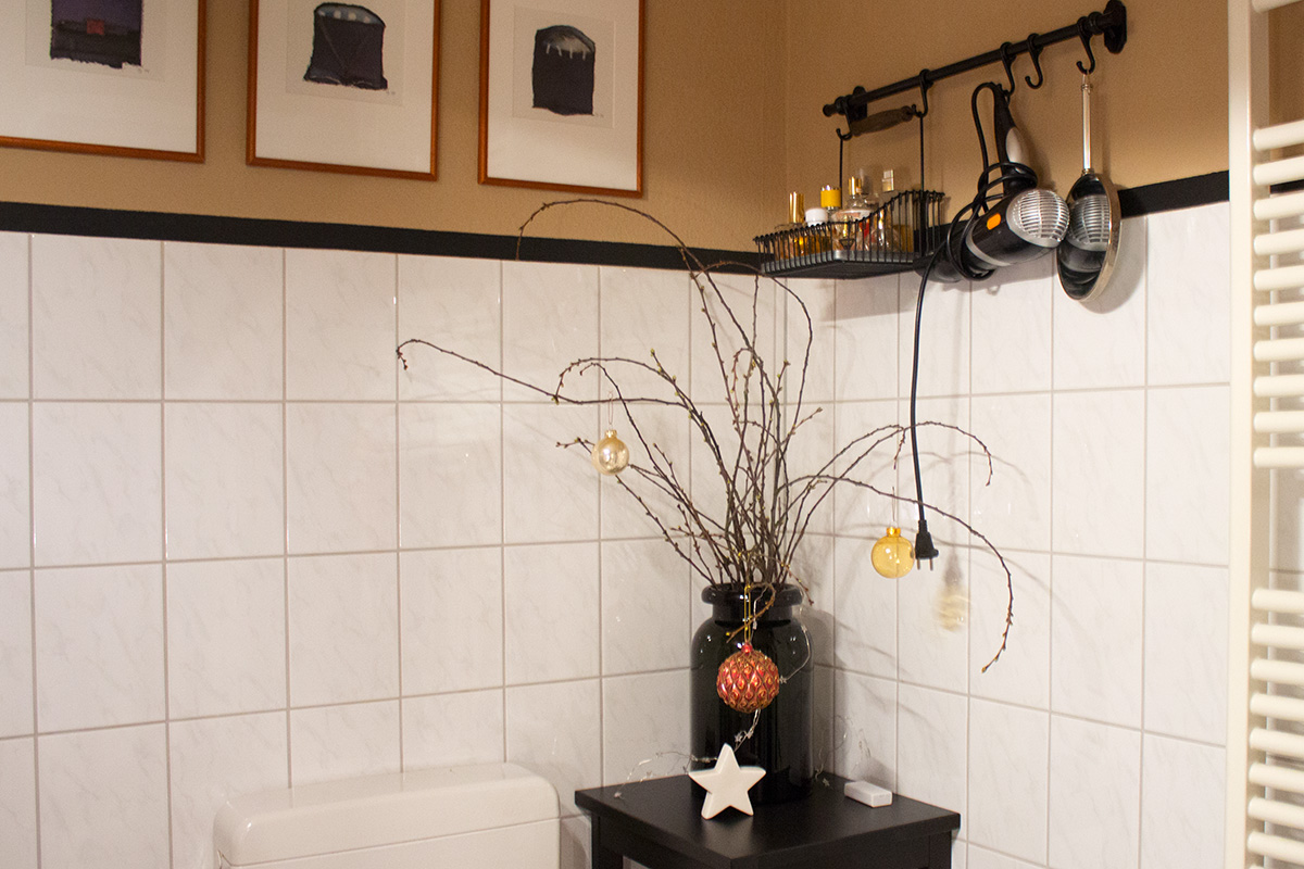 Farbich gestrichenes Badezimmer mit Frühlingsstrauss und Accessoires