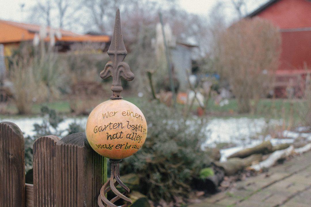 """Ausschnitt aus einem Schrebergarten: ein gusseiserner Stab mit einer angebrachten Tonkugel darauf der Spruch """"Wer einen Garten besitzt, hat alles, was er braucht."""""""