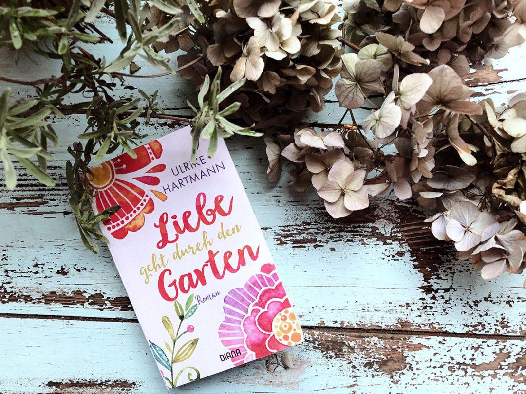"""Ein Buch mit dem Titel """"Liebe geht durch den Garten"""" liegt auf einem türkisfarbenen Gartentisch umringt von Lavendel und getrockneten Hortensien"""