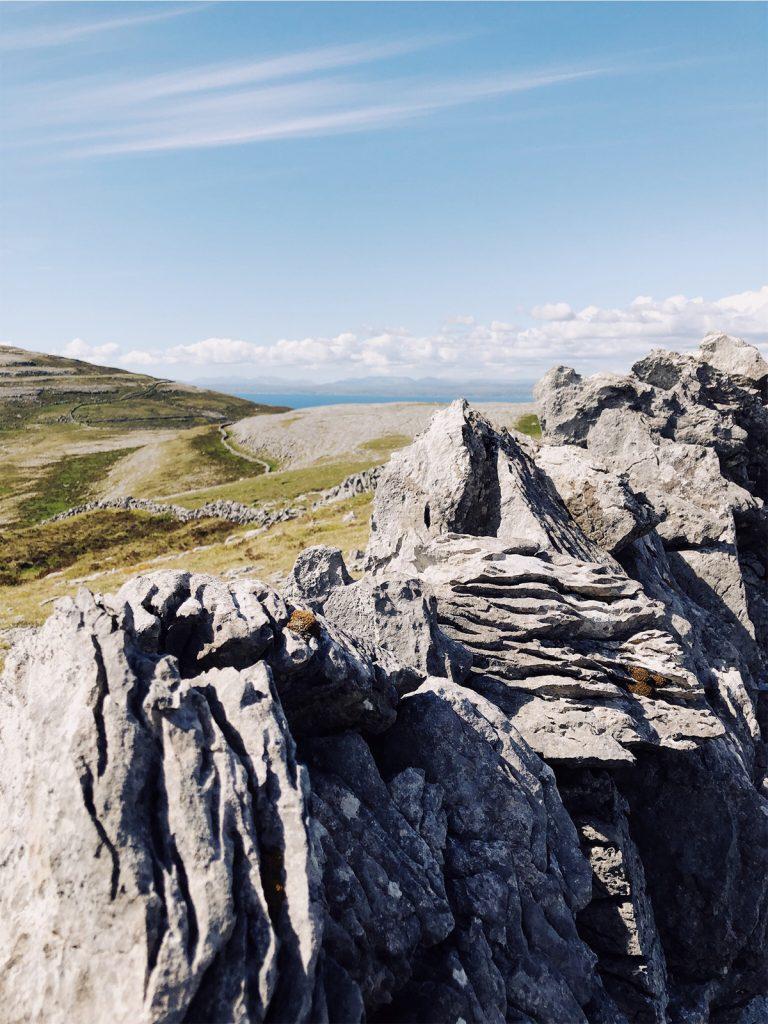 Irland Ansicht Burren grüne Hügel und Steinmauer