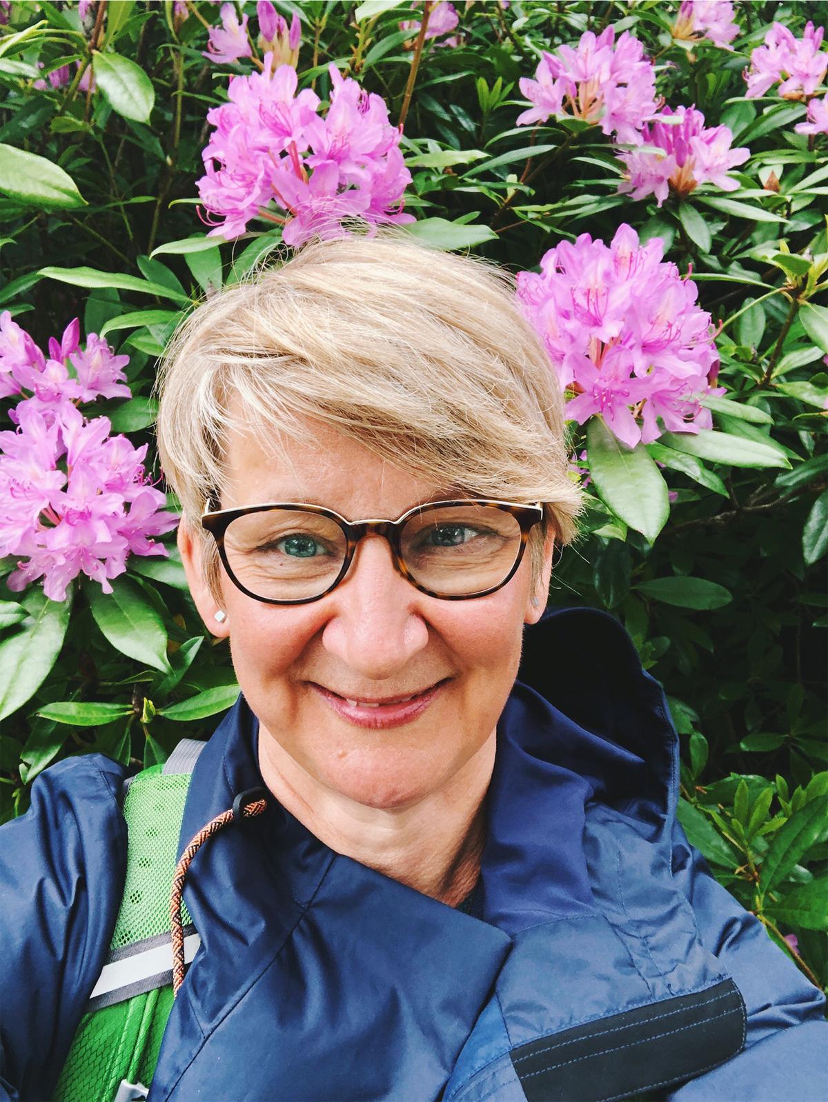 Irland Anke Hedfeld steht vor einem Rhododendron