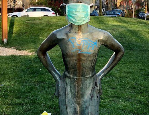 Eine weibliche Bronzestatue in einem Park trägt einen Mundschutz – Corona 2020