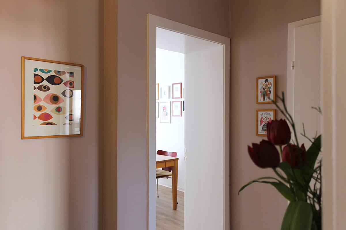 Blick in einen rosa gestrichenen Flur Bilder an der Wand im Vordergrund Blumen