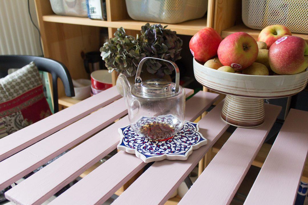 Ein Stillleben in einer Küche: Ein Hortensienstrauch, eine Schale mit Äpfeln, eine Teekanne auf einem rosa gestrichenen Tisch
