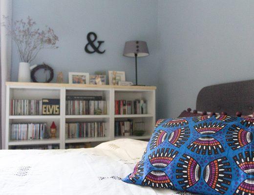 Ein Ausschnitt aus einem Schlafzimmer mit einem bunten Kissen im Vordergrund