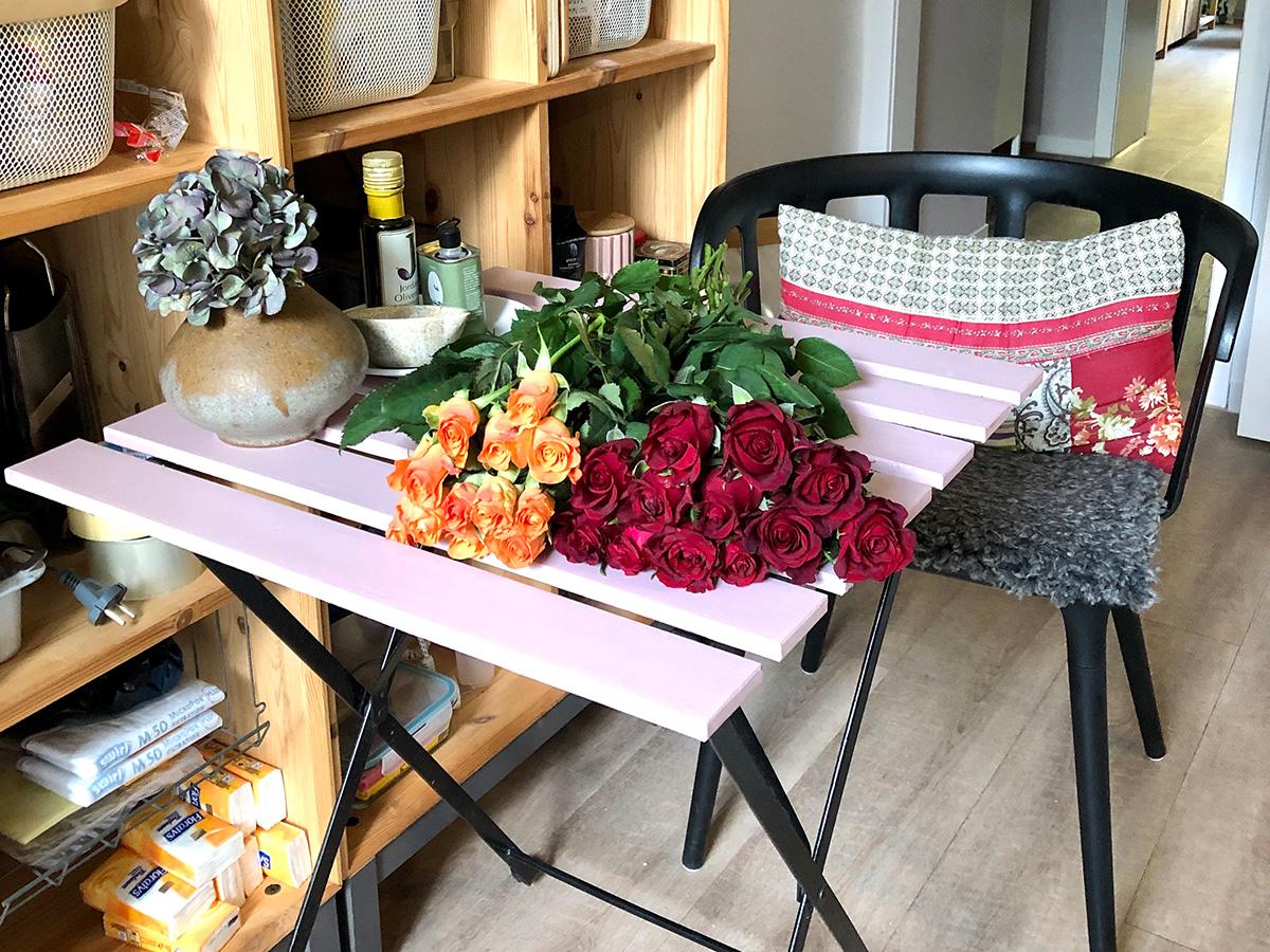 Zwei verschiedene Rosensträuße liegen auf einem Tisch in einer Küche