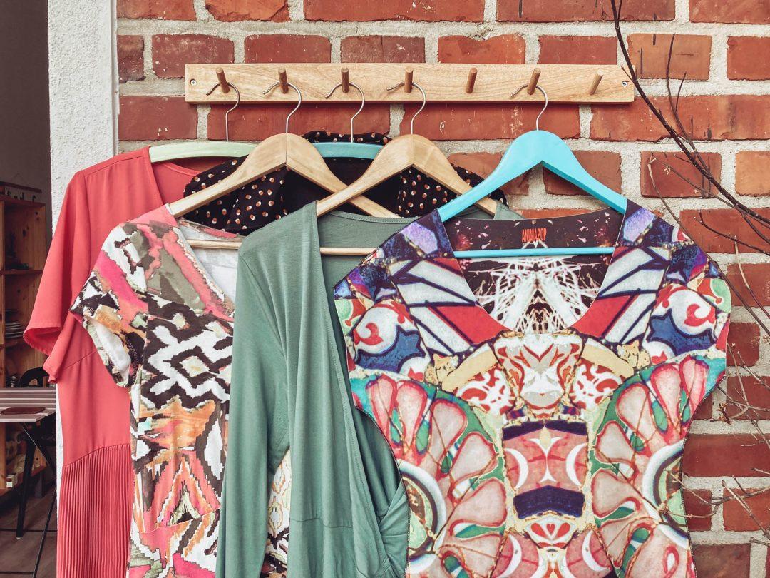 Verschiedene bunte Kleider hängen auf Bügeln